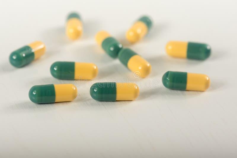 Pilules vertes et jaunes de capsule de tramadol sur le fond blanc Les capsules de tueur de douleur ont appel? image libre de droits