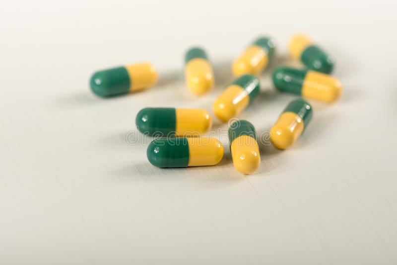 Pilules vertes et jaunes de capsule de tramadol sur le fond blanc Les capsules de tueur de douleur ont appel? images libres de droits