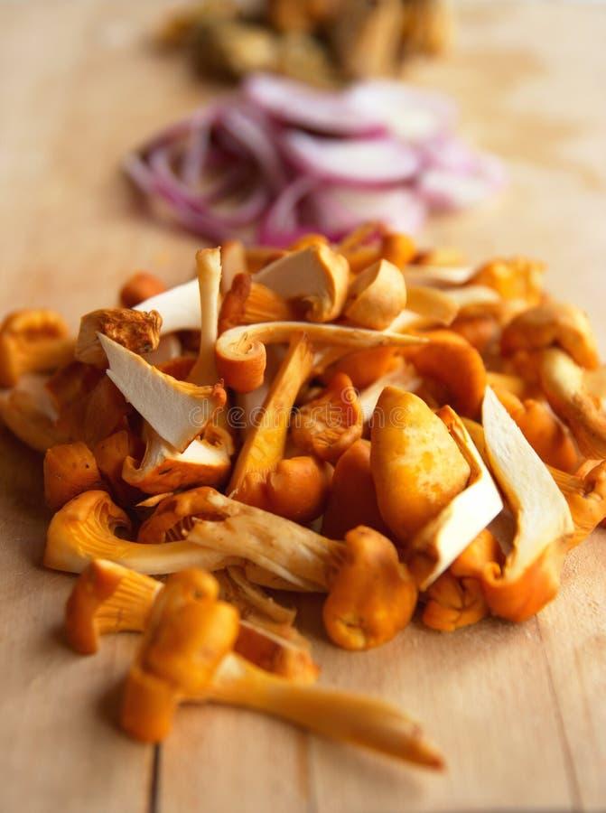 Pilze und Zwiebeln auf Ausschnittvorstand stockfotos