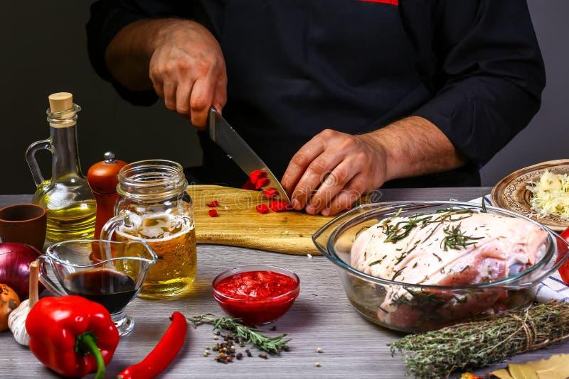 Pimentão afiado do cozinheiro chefe no fundo de madeira da tabela Cozimento bávaro da junta da carne de porco Conceito caseiro da foto de stock royalty free