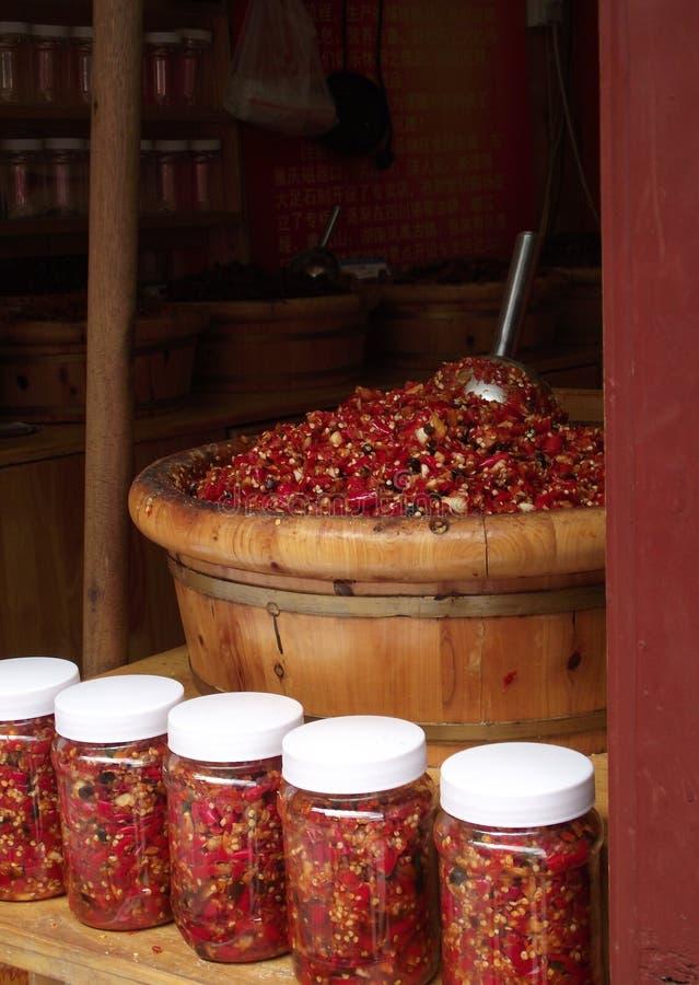 Pimentão de Yunnan em uns frascos e no volume na cubeta de madeira tradicional em Lijiang, Yunnan imagens de stock