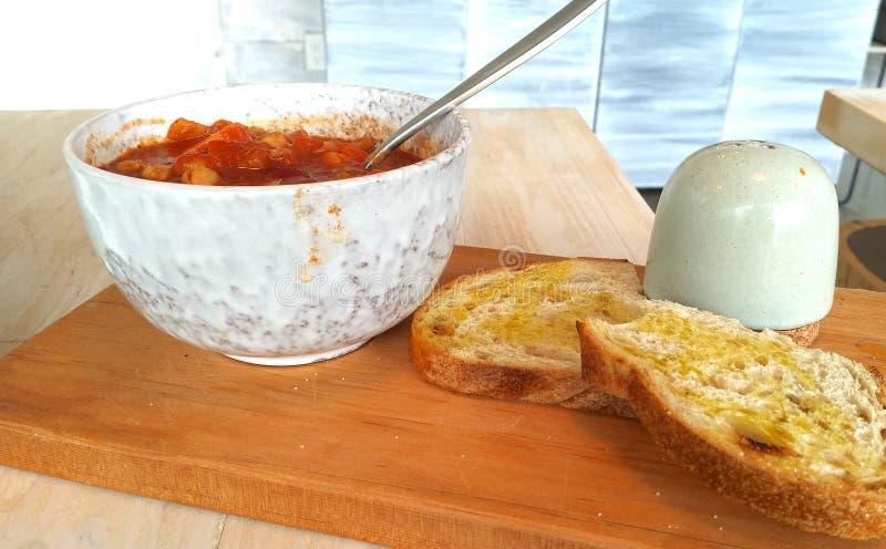 Piment de Vegan dans une cuvette se reposant sur une planche à découper avec du pain grillé du côté photographie stock