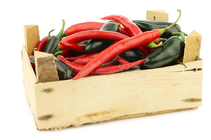Piment et jalapeno d'un rouge ardent de poivrons verts dans une boîte en bois photo libre de droits