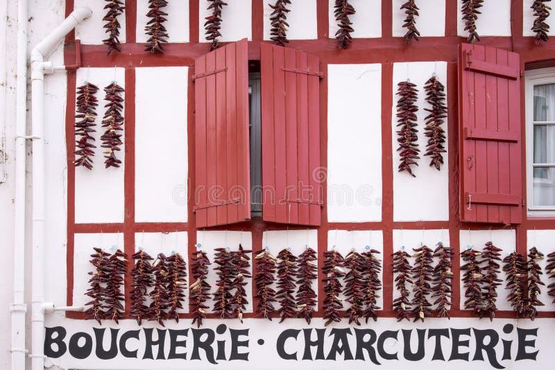 A pimenta de Espelette amarra a suspensão contra a fachada de um açougue em Espelette fotos de stock