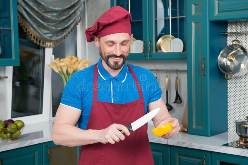 Pimenta de sino amarelo cortada indo do cozinheiro Homem do cozinheiro chefe que cozinha vegetais na cozinha Começo do homem que  fotografia de stock