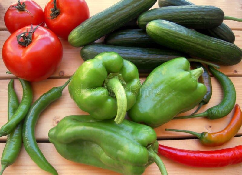Pimenta doce, tomates, pepinos e pimenta de pimentão verdes na tabela rústica imagem de stock