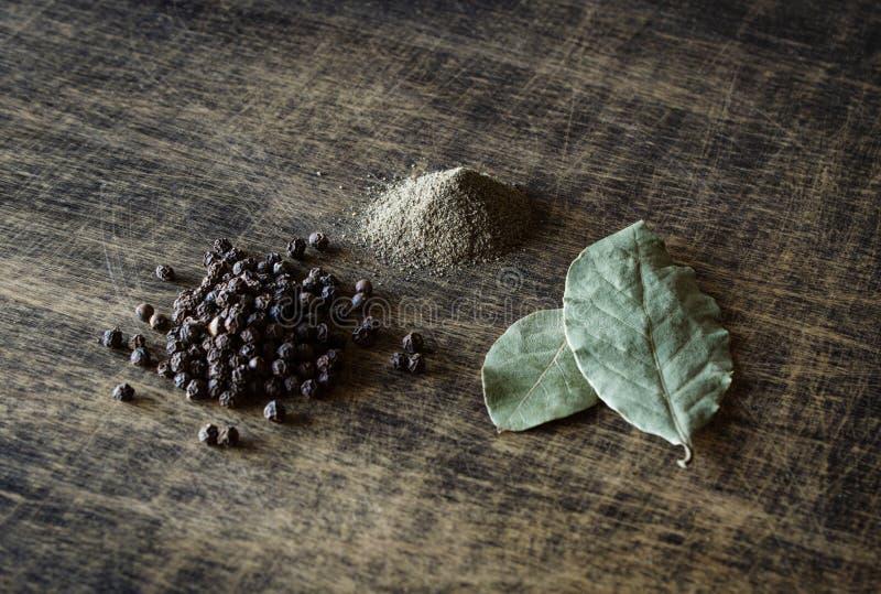 Pimenta e folhas de louro em uma tabela marrom Esmagado e não esmagado spice fotografia de stock royalty free