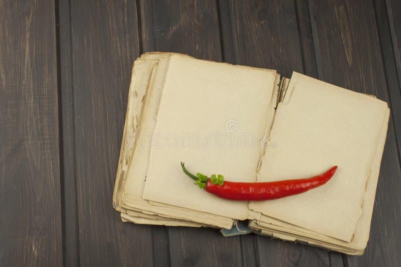 Pimenta fria com o livro da receita no fundo de madeira da tabela fotografia de stock