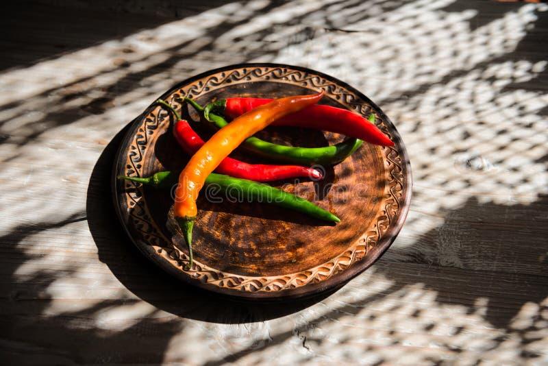 Pimenta multicolor em placa de cerâmica imagem de stock