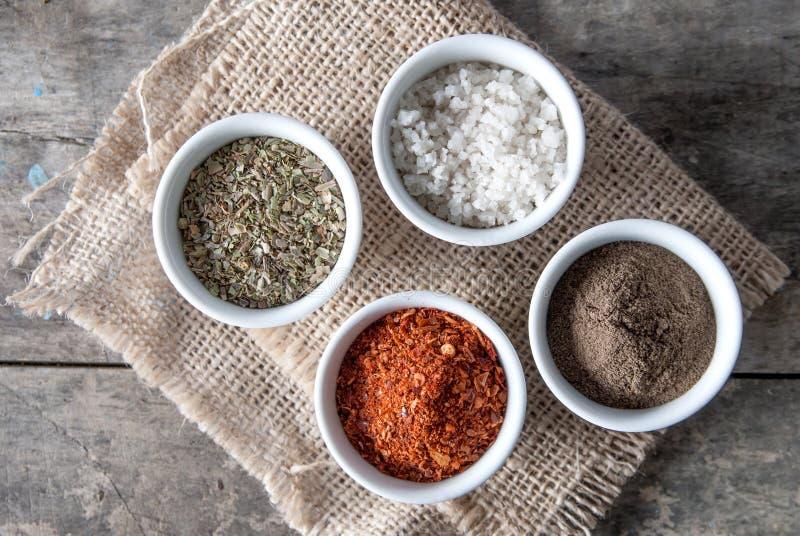 Pimenta, orégano e sal do cozimento em umas bacias imagens de stock