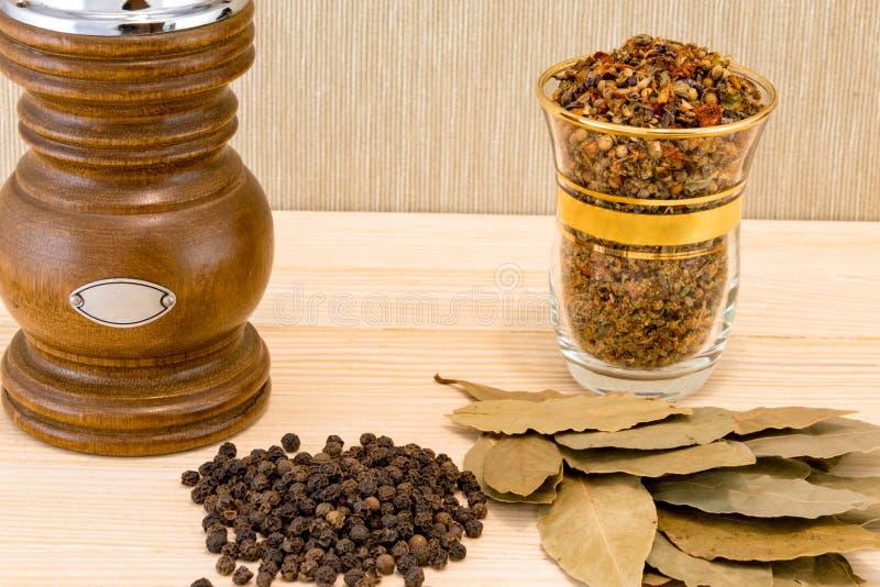 Pimenta preta e folha de louro seca, especiarias no fundo de madeira fotos de stock royalty free