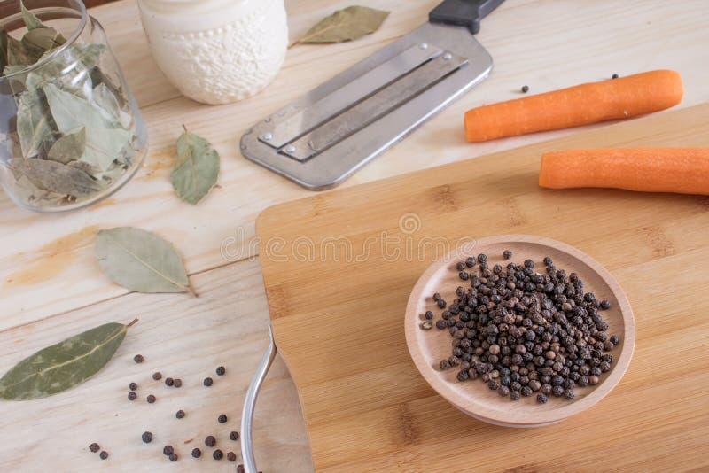 Pimenta preta e folhas de louro secas ao lado das cenouras em uma tabela de madeira ao lado de uma faca e do outro equipamento da fotografia de stock