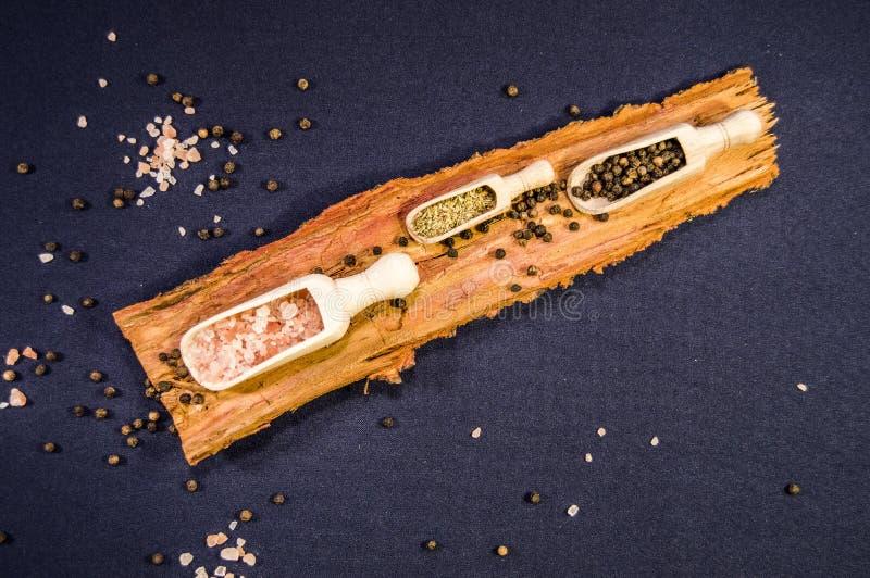 Pimenta, sal e manjeric?o na colher de madeira fotografia de stock royalty free