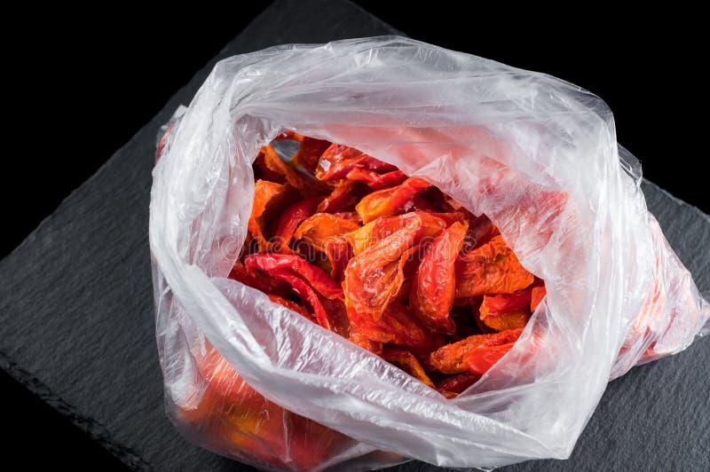 Pimenta vermelha congelada em um saco de plástico em uma placa de pedra em um fundo preto, isolado imagem de stock royalty free