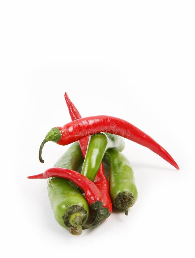 Pimentas agradáveis frescas vermelhas e verdes no fundo branco - muito quente! imagem de stock royalty free