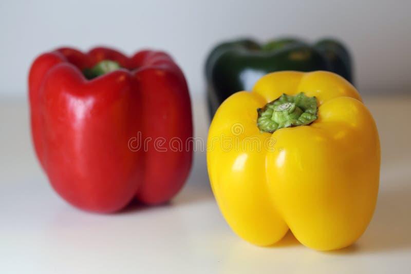 Pimentas de Bell frescas verdes, amarelas e vermelhas em uma superfície branca imagem de stock