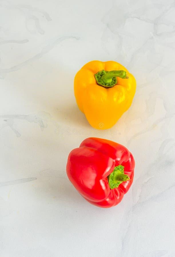 Pimentas de Bell vermelha e amarela/capsicum no fundo Cinzento-branco imagem de stock royalty free