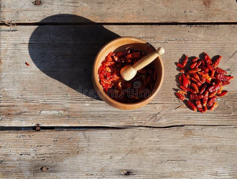 Pimentas de pimentão secadas com almofariz e pilão em tabela de madeira gasta sob a luz solar fotografia de stock royalty free