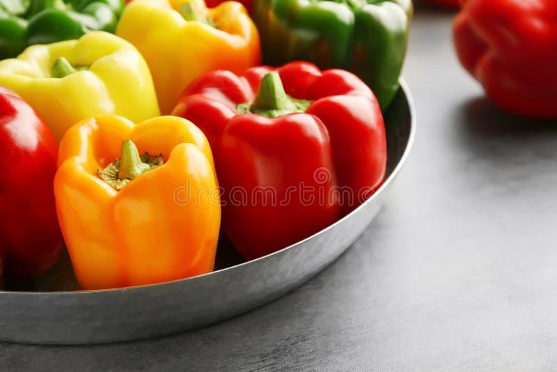 Pimentas de sino doce vermelhas, verdes e amarelas na tabela, foto de stock
