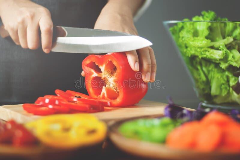 Pimentas de sino vermelhas do corte fêmea Cozinhando o alimento do vegetariano sagacidade saudável fotografia de stock royalty free