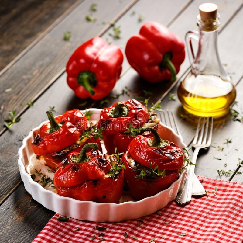 Pimentas de sino vermelhas Roasted enchidas com arroz, cogumelos e queijo em uma tabela de madeira fotos de stock
