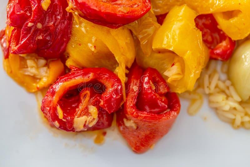 Pimentas doces fritadas amarelas vermelhas cozinhadas e um alho em uma placa branca Alimento do vegetariano imagens de stock