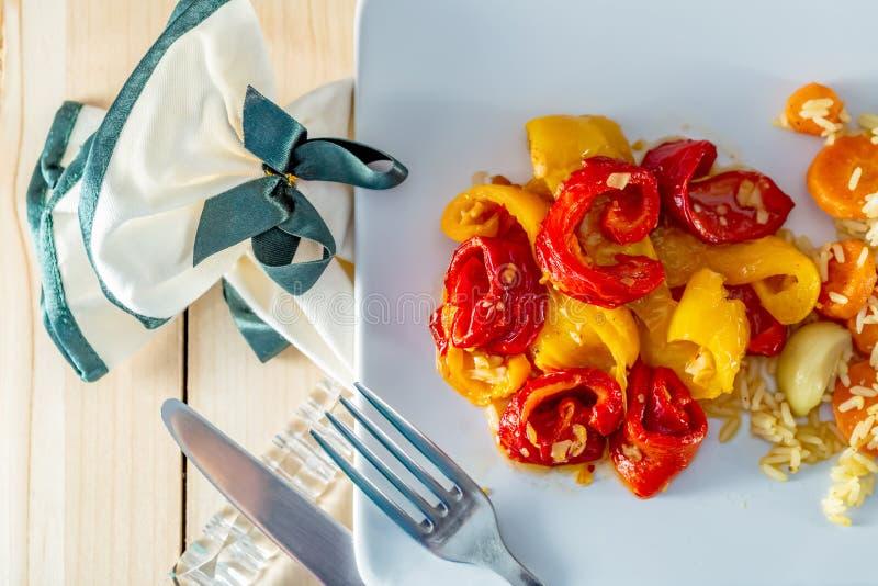 Pimentas e arroz branco cozinhado, cenouras deliciosas em uma placa cerâmica branca e forquilha e faca Guardanapo com uma curva imagens de stock royalty free