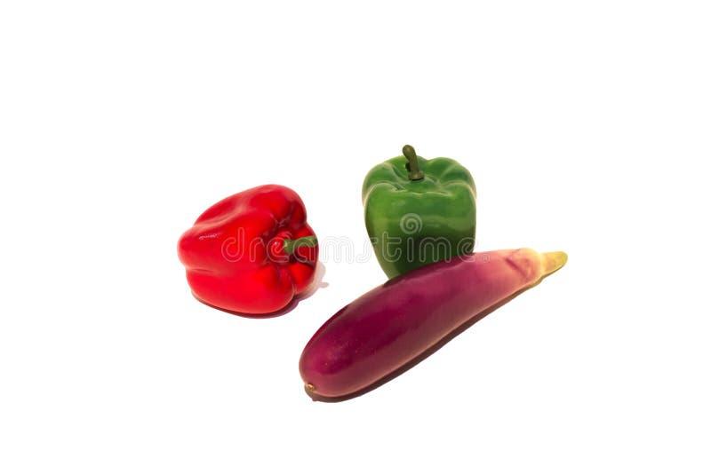 Pimentas plásticas e abobrinha vermelhos e verdes isolados em um fundo branco imagens de stock royalty free