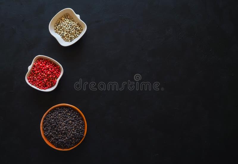 Pimentas pretas, cor-de-rosa e brancas em uma bacia A vista da parte superior fotografia de stock