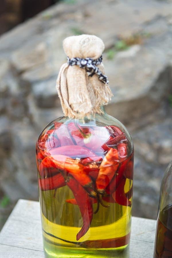 Pimentas vermelhas enlatadas em uma garrafa com óleo, conservas caseiros fotos de stock