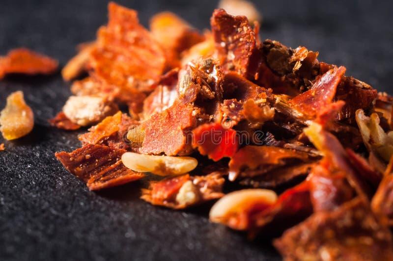 Pimentas vermelhas esmagadas com sementes em um close-up escuro do fundo foto de stock royalty free