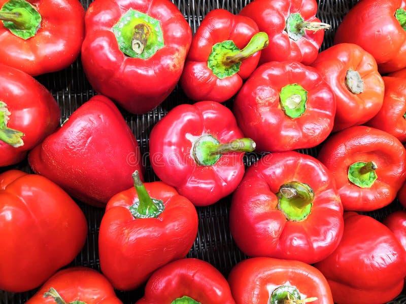 Pimentas vermelhas maduras em uma cesta de vime em um fundo escuro foto de stock