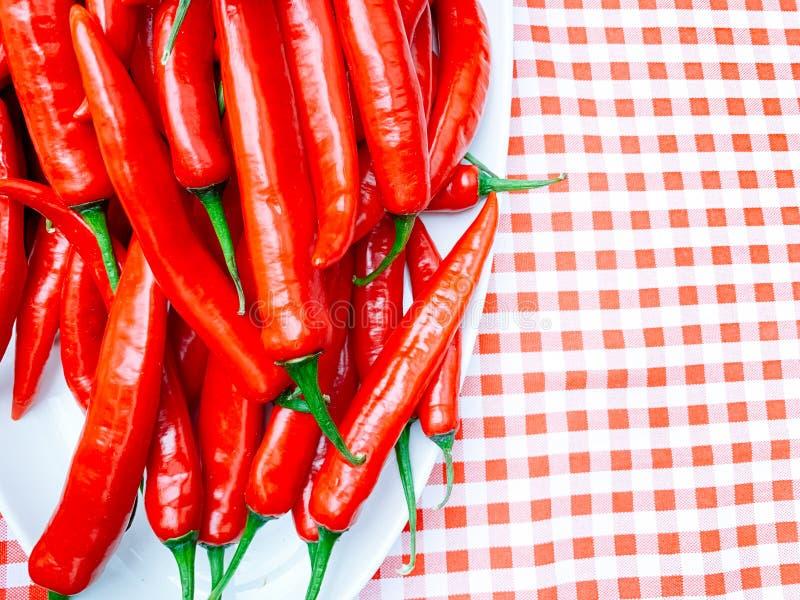 Pimentas vermelhas ou pimentões bonitos no fundo vermelho da toalha de mesa da manta fotografia de stock royalty free