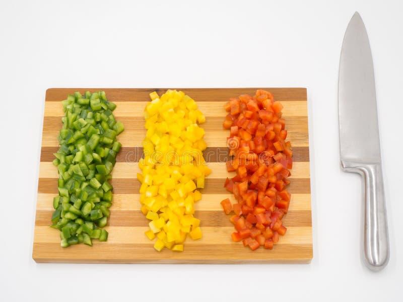 Pimentos doces ou pimentões, de cor vermelha, verde e amarela, cortados numa prancha de corte de madeira e numa faca de corte fotos de stock