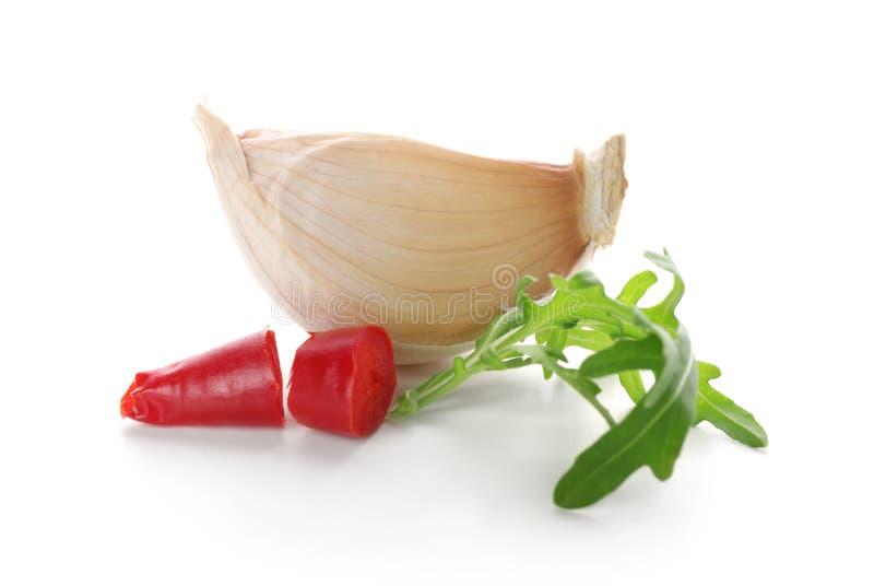 Pimienta de chile, ajo y arugula en el fondo blanco fotografía de archivo