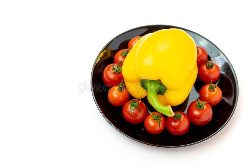 Pimienta dulce amarilla con los tomates en una placa negra aislada en el fondo blanco Composici?n de pimientas amarillas y de tom imagen de archivo