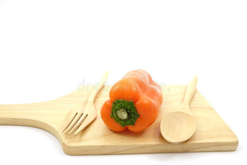 Pimienta dulce anaranjada en la placa de madera con la cuchara de madera y la bifurcación de madera imagenes de archivo