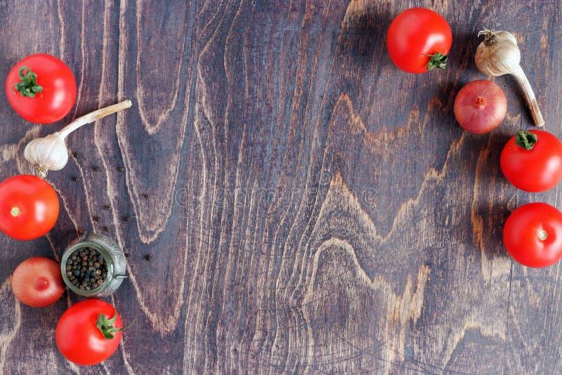 Pimienta negra, ajo, cebolla y tomates en fondo de madera Productos para cocinar imágenes de archivo libres de regalías