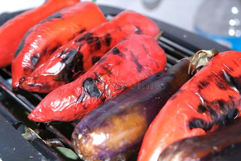 Pimienta roja, berenjena en parrilla de la barbacoa en el carbón de leña caliente y fuego Preparaci?n de la comida sana el d?a de fotos de archivo
