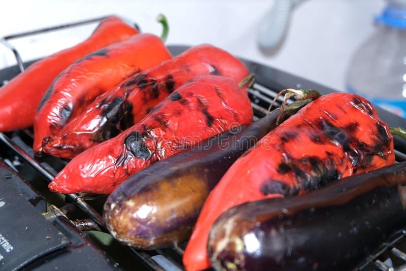 Pimienta roja, berenjena en parrilla de la barbacoa en el carbón de leña caliente y fuego Preparaci?n de la comida sana el d?a de imágenes de archivo libres de regalías