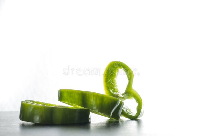 Pimienta verde cortada en el fondo blanco fotografía de archivo