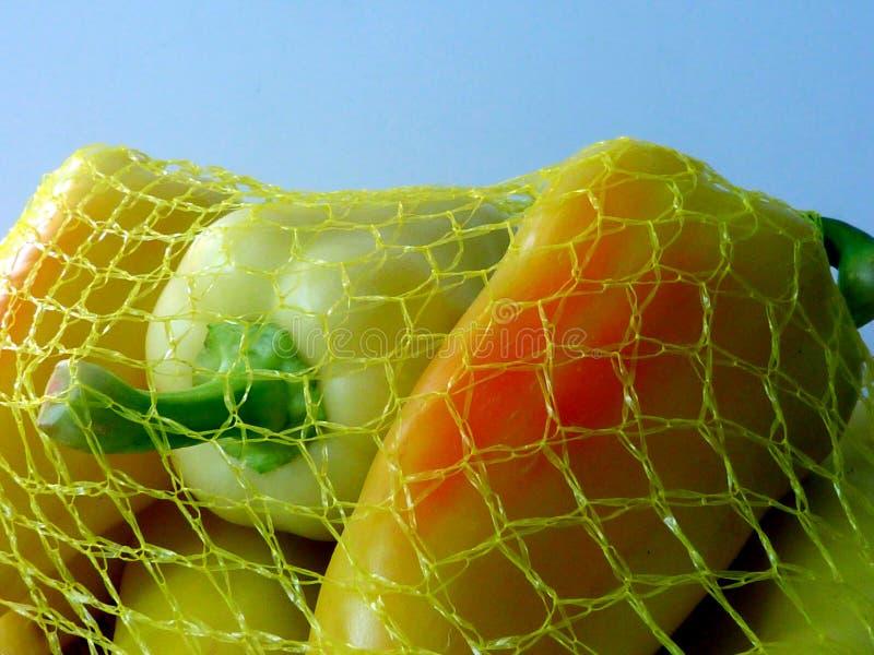 pimientas amarillas dulces frescas embaladas en red amarilla del vinilo fotos de archivo