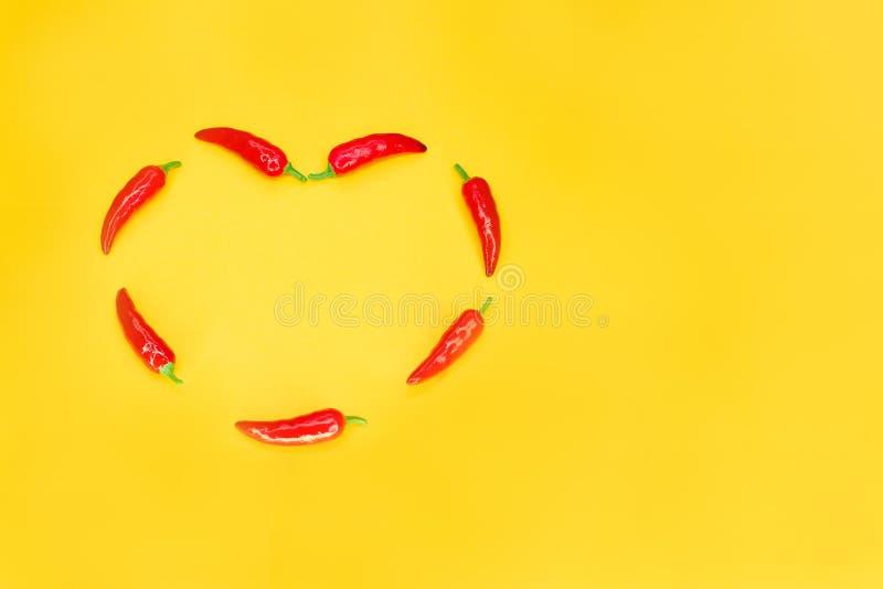 Pimientas de chile rojo en forma de corazón en fondo amarillo con el espacio de la copia Concepto del amor apasionado foto de archivo