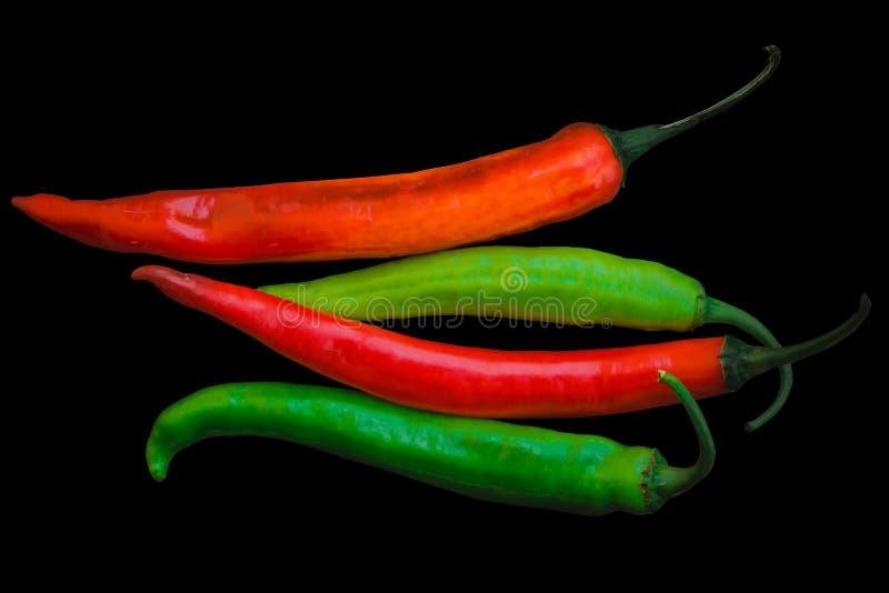 Pimientas de chiles grandes rojas y verdes aisladas en negro fotografía de archivo