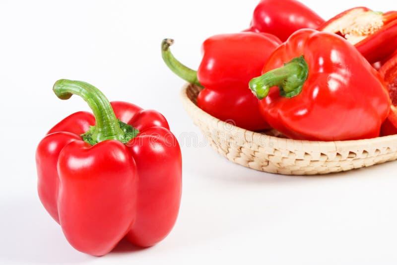 Pimientas maduras rojas con la cesta de mimbre en el fondo blanco, nutrición sana fotografía de archivo