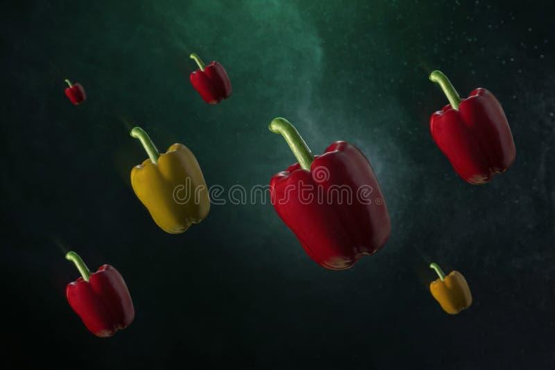 Pimientas rojas y amarillas de la paprika aisladas en fondo del verde de la pendiente fotos de archivo libres de regalías