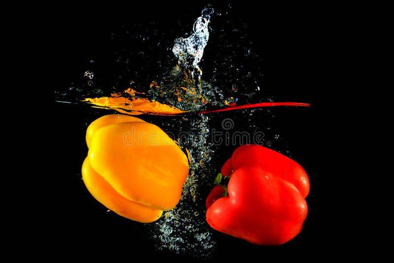 Pimientas rojas y amarillas que caen en agua fotografía de archivo libre de regalías