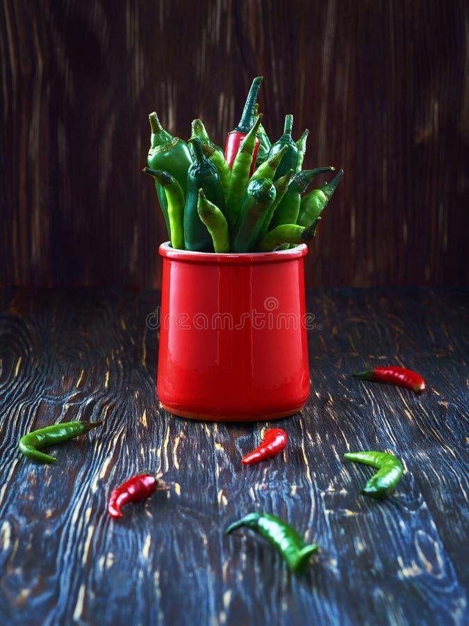 Pimientas verdes en una taza roja en una tabla de madera imágenes de archivo libres de regalías