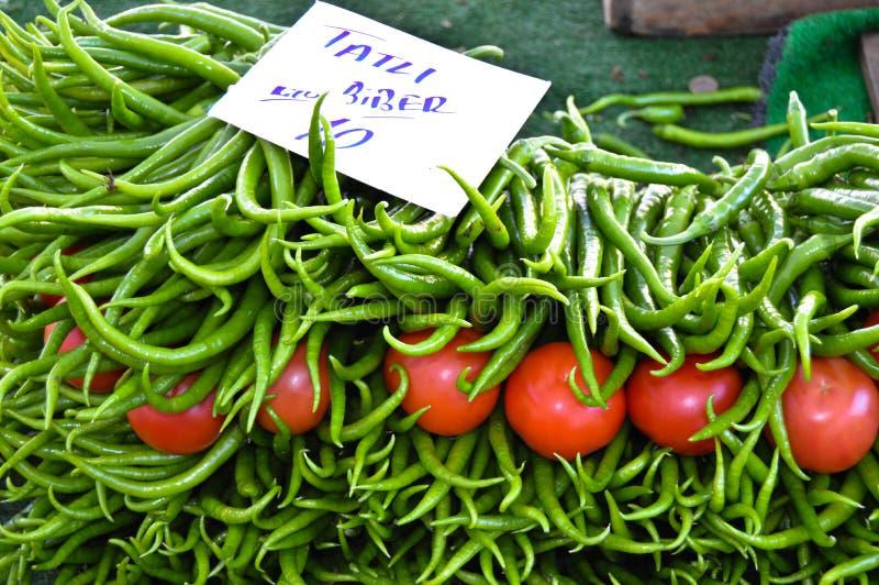 Pimientas verdes frescas y tomates vendidos en el mercado de la vecindad fotografía de archivo