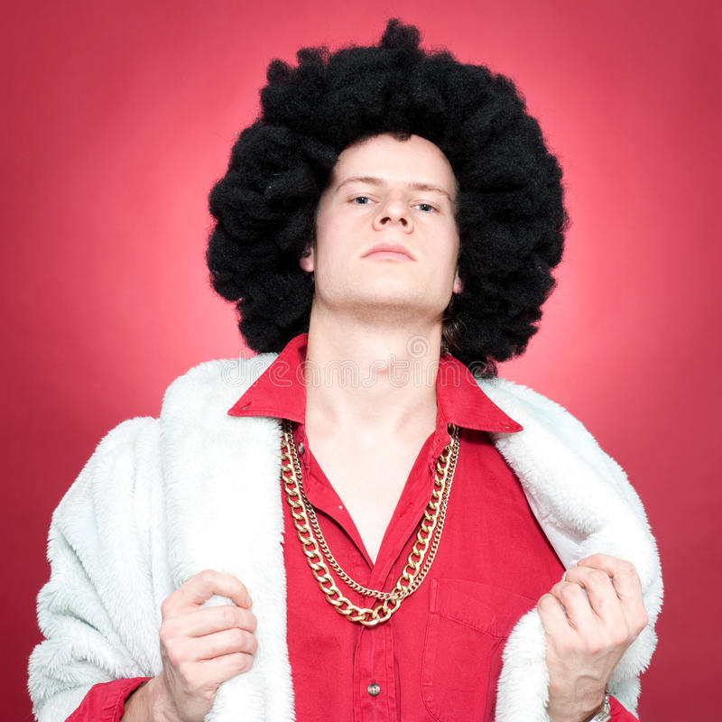 Pimp. Arrogantly looking man, wearing a wig and a golden chain stock photo